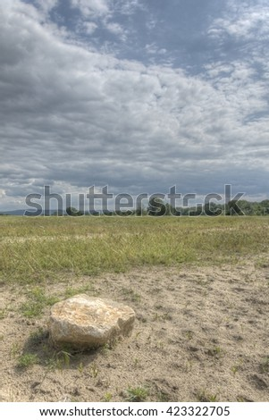 Blue sky green meadow with stone rock. - stock photo