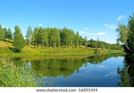 Blue sky, is reflected in the quiet surface of forest lake.