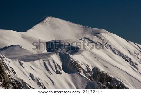 Blue sky, mountain peak in snow in winter in slovenian alps - stock photo