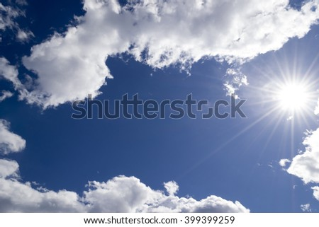 Blue sky. Nature background. Bright sun rays in the sky. Sun shine through clouds. Bright sun causing lens flare - stock photo