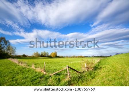 blue sky over fence on sunny dutch farmland, Holland - stock photo