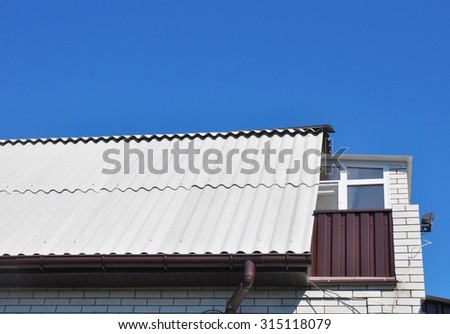 Blue sky over the dangerous asbestos new roof tiles with roof window, dormer and small balcony. Use of asbestos in buildings is bad for health. - stock photo