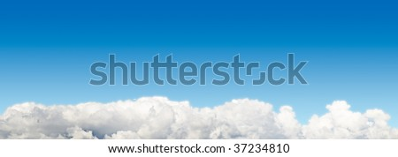 Blue sky panoramic background with cloudscape at the bottom. - stock photo