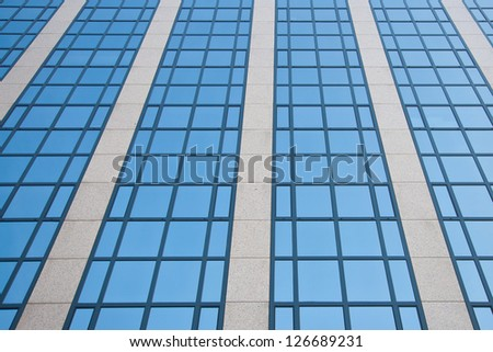 blue sky reflected in grid formed by windows - stock photo