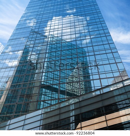 blue sky reflected in modern building mirror glass wall - stock photo