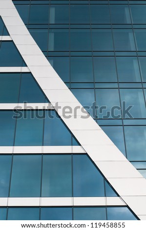 Blue sky reflected in the windows of office building - stock photo