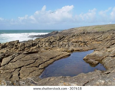 Blue sky, sea and beautifull rocks forming a small lake.
