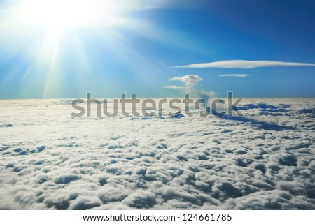 Blue sky, sun and clouds. Plane view above the earth, can be used for background - stock photo