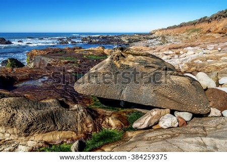 Blue sky, tidal pools, green algae, rock and unusual geological formations at low tide, along the rugged Big Sur coastline, near Monterey, CA. on the California Central Coast. - stock photo