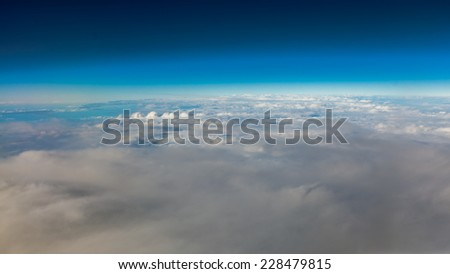 Blue sky. View from window of airplane flying in clouds. Skyscape cloudscape. Bird's eye.