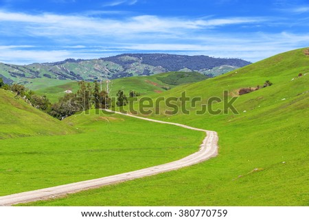 Blue sky, white clouds, green hills, grass & fields on a winding rural / country road, on the California Central Coast near Cambria, CA. - stock photo