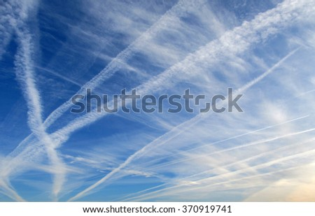 blue sky with airy clouds and numerous traces of jets