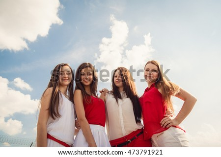 Blue sky with bright blue clouds hangs over pretty girls dressed in red and white tones