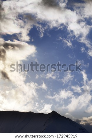 Blue sky with clouds and mountains in evening. Caucasus Mountains, Georgia, ski resort Gudauri. - stock photo