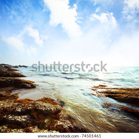Blue sky with clouds and rocks in water - stock photo