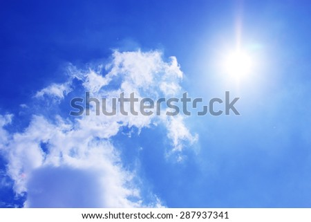 Blue sky with clouds and sun. - stock photo