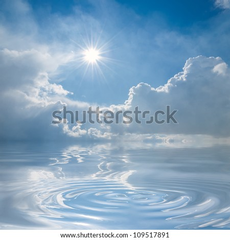 Blue sky with clouds and sun reflection in water with waves - stock photo
