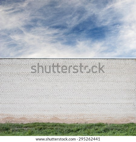 Blue sky with clouds behind the huge wall and green grass background - stock photo