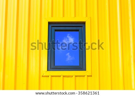 Blue sky with clouds reflected in glass windows of yellow container wall. - stock photo