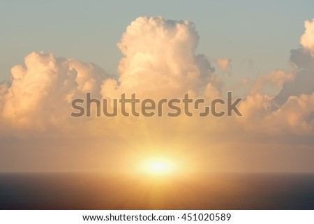Blue sky with clouds, sea and sun on the horizon - stock photo