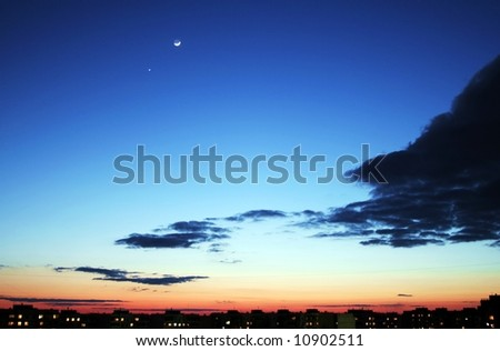 Blue sky with clouds. Sunset above the roofs of houses. - stock photo