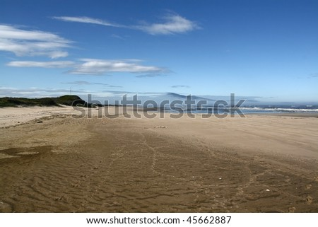 blue sky with clouds under the broad sandy seashore in the day-time in summer, sea in the distance