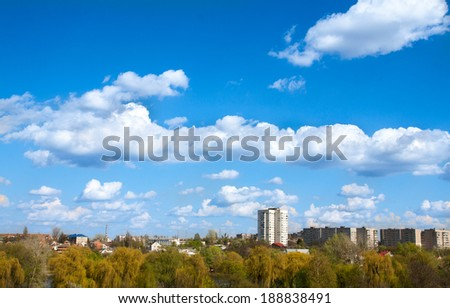 blue sky with field of green grass and city on the horizon - stock photo