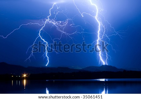 Blue sky with lightning striking hills behind the lake. - stock photo