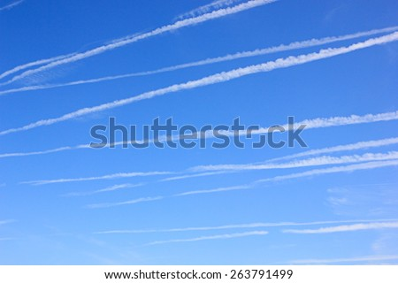 Blue sky with many contrails from aircraft - stock photo