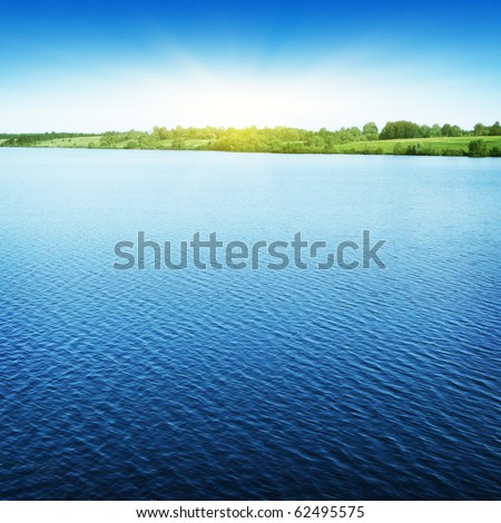 Blue sky with sun over water.