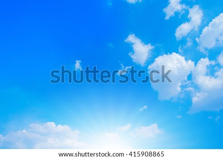 Blue sky with white clouds and sun shining out.