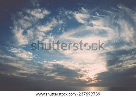 blue sky with white clouds closeup over the sea - retro, vintage style look