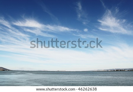 Blue sky with white clouds over sea - stock photo