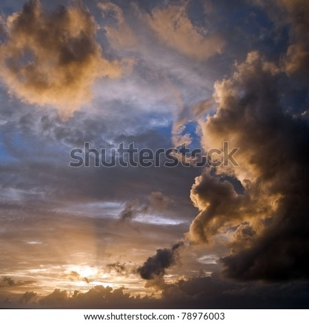 Blue sky with yellow backlit clouds coming from the sun that is shining through with light rays. Square background composition. - stock photo