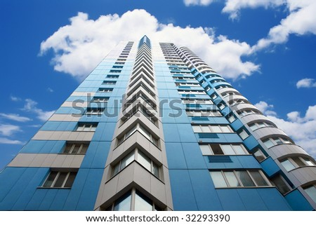 blue skyscraper in front of cloudy sky - stock photo