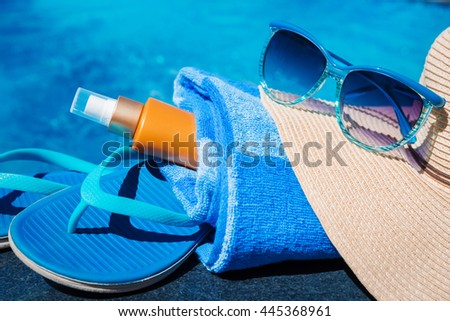 Blue slippers, sunsscreen cream, straw hat and sun glasses near swimming pool - holiday concept - stock photo