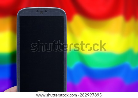 Blue smartphone and LGBT flag blur background. Idea for Valentines Day messages, LGBT love, lovers, love apps, Internet, blogs and others. - stock photo