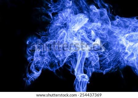 Blue smoke on black background - stock photo