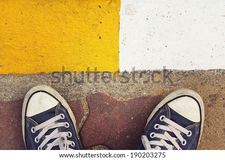 Blue sneakers from an aerial view on concrete block pavement. Top view, feeling between choose, choice. - stock photo