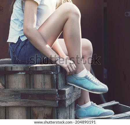 Blue sneakers on girl legs on the grunge background. Close up - stock photo