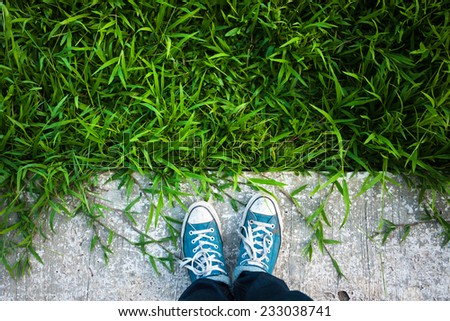Blue Sneakers shoes walking on green grass top view - stock photo