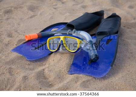 Blue snorkeling equipment on sand by the seaside - stock photo