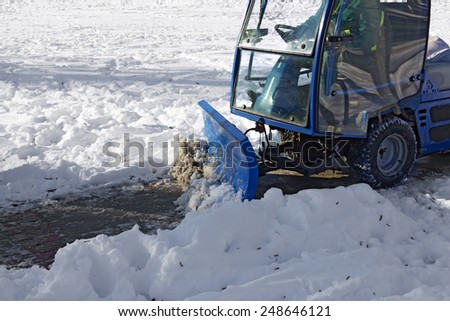 Blue snowplow removing snow from sidewalk and sprinkled salt antifreeze - stock photo