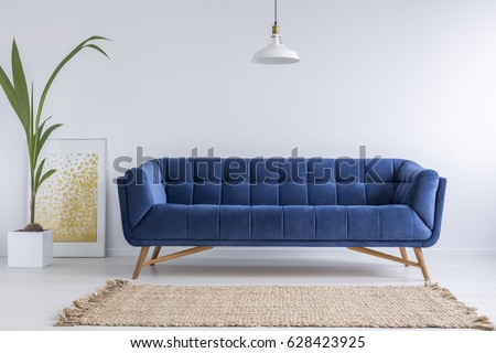 Blue sofa and wicker carpet in white simple living room