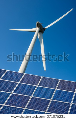 Blue solar cells and wind turbine, environment and climate change concept - stock photo