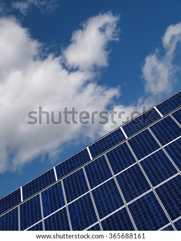 Blue solar cells in slant perspective against blue and white sky