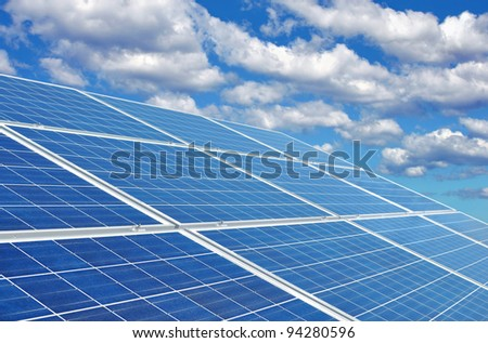 Blue solar panels creating eco-friendly green energy from the sun. - stock photo