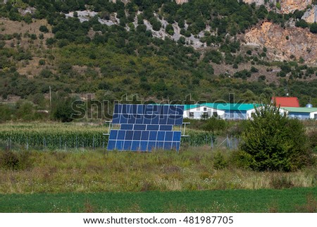 Blue solar panels in field facing the sun