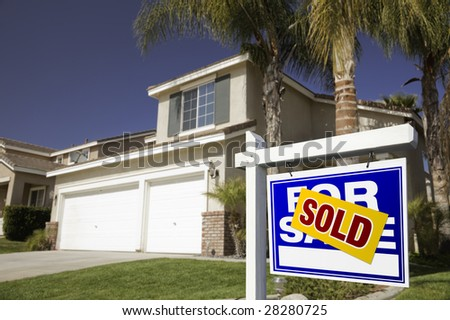 Blue Sold For Sale Real Estate Sign in Front of House. - stock photo