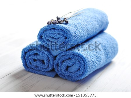 Blue spa towels pile with lavender on white wooden background - stock photo